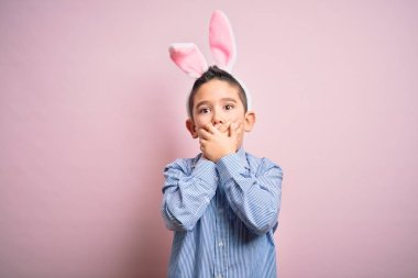 Young little boy kid wearing easter bunny ears over isolated pink background shocked covering mouth with hands for mistake. Secret concept.