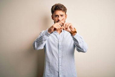 Young handsome man with beard wearing striped shirt standing over white background Rejection expression crossing fingers doing negative sign