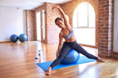 Middle age beautiful sportswoman smiling happy. Doing exercise using fitness ball in a class of yoga at gym