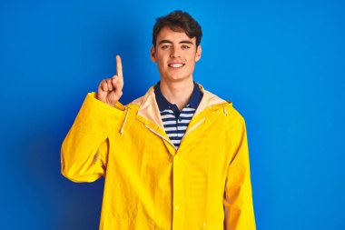 Teenager fisherman boy wearing yellow raincoat over isolated background showing and pointing up with finger number one while smiling confident and happy.