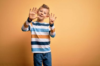 Young little caucasian kid with blue eyes wearing colorful striped shirt over yellow background showing and pointing up with fingers number nine while smiling confident and happy.
