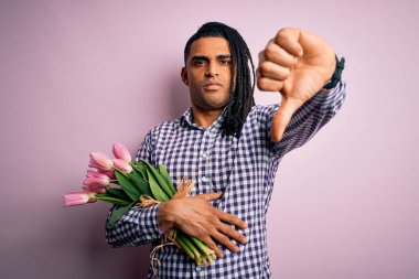 Young african american afro romantic man with dreadlocks holding bouquet of pink tulips looking unhappy and angry showing rejection and negative with thumbs down gesture. Bad expression.