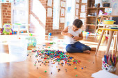 Adorable toddler playing with building blocks toy around lots of toys at kindergarten