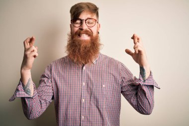 Handsome Irish redhead business man with beard wearing glasses over isolated background gesturing finger crossed smiling with hope and eyes closed. Luck and superstitious concept.
