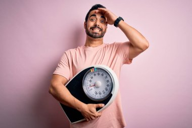 Young handsome slim sportsman with beard holding scale over isolated pink background stressed with hand on head, shocked with shame and surprise face, angry and frustrated. Fear and upset for mistake.
