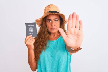 Middle age mature tourist woman holding United States passport over isolated background with open hand doing stop sign with serious and confident expression, defense gesture