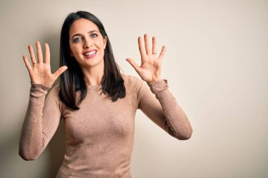 Young brunette woman with blue eyes wearing casual sweater over isolated white background showing and pointing up with fingers number ten while smiling confident and happy.