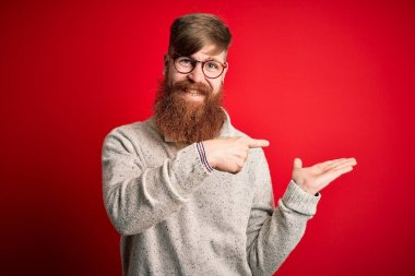 Handsome Irish redhead man with beard wearing casual sweater and glasses over red background amazed and smiling to the camera while presenting with hand and pointing with finger.