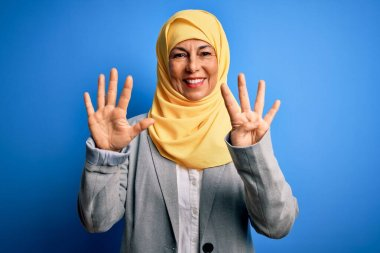 Middle age brunette business woman wearing muslim traditional hijab over blue background showing and pointing up with fingers number nine while smiling confident and happy.