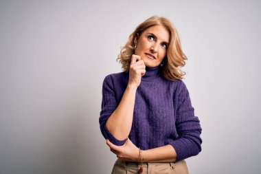 Middle age beautiful blonde woman wearing purple turtleneck sweater over white background with hand on chin thinking about question, pensive expression. Smiling with thoughtful face. Doubt concept.