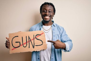 Young african american man asking for peace holding banner with prohibited guns message very happy pointing with hand and finger