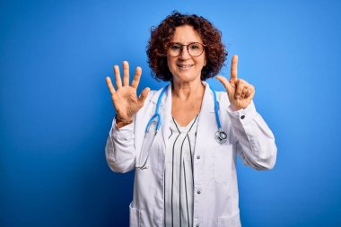 Middle age curly hair doctor woman wearing coat and stethoscope over blue background showing and pointing up with fingers number seven while smiling confident and happy.