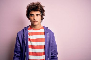 Young man wearing striped t-shirt and purple sweashirt over isolated pink background with serious expression on face. Simple and natural looking at the camera.