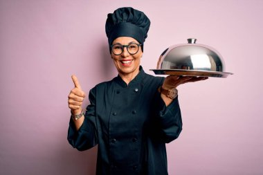 Middle age brunette chef woman wearing cooker uniform and hat holding tray dome happy with big smile doing ok sign, thumb up with fingers, excellent sign