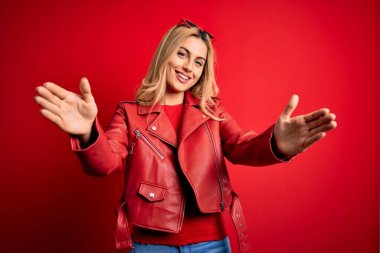 Young beautiful blonde woman wearing casual jacket standing over isolated red background looking at the camera smiling with open arms for hug. Cheerful expression embracing happiness.