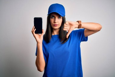 Young delivery woman with blue eyes wearing cap holding smartphone with angry face, negative sign showing dislike with thumbs down, rejection concept