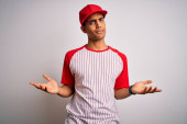 Young handsome african american sportsman wearing striped baseball t-shirt and cap clueless and confused with open arms, no idea concept.