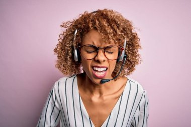 African american curly call center agent woman working using headset over pink background with hand on stomach because nausea, painful disease feeling unwell. Ache concept.