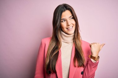 Young beautiful businesswoman wearing casual turtleneck sweater and jacket smiling with happy face looking and pointing to the side with thumb up.
