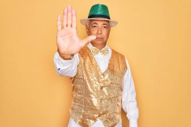 Middle age senior grey-haired man wearing Brazilian carnival custome over yellow background doing stop sing with palm of the hand. Warning expression with negative and serious gesture on the face.
