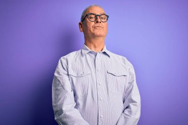 Middle age handsome hoary man wearing striped shirt and glasses over purple background Relaxed with serious expression on face. Simple and natural looking at the camera.