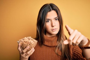 Young beautiful girl holding bowl of healthy cornflakes cereals over yellow background pointing with finger to the camera and to you, hand sign, positive and confident gesture from the front