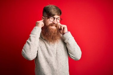 Handsome Irish redhead man with beard wearing casual sweater and glasses over red background covering ears with fingers with annoyed expression for the noise of loud music. Deaf concept.