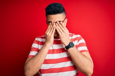 Young handsome man wearing casual striped t-shirt and glasses over isolated red background rubbing eyes for fatigue and headache, sleepy and tired expression. Vision problem