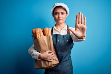 Young beautiful baker woman with blue eyes holding paper bag with  bread with open hand doing stop sign with serious and confident expression, defense gesture