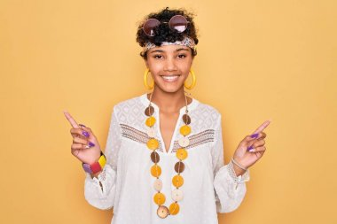 Young beautiful african american afro hippie woman wearing sunglasses and accessories smiling confident pointing with fingers to different directions. Copy space for advertisement