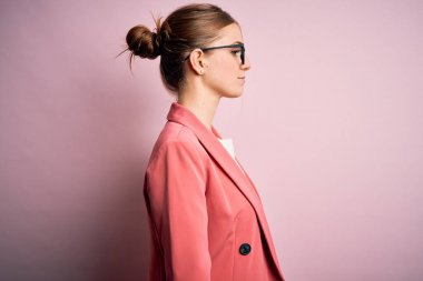Young beautiful redhead woman wearing jacket and glasses over isolated pink background looking to side, relax profile pose with natural face with confident smile.