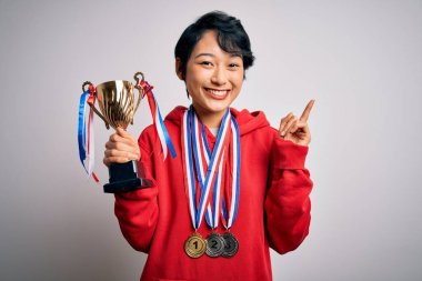 Young beautiful asian girl winner holding trophy wearing medals over white background surprised with an idea or question pointing finger with happy face, number one
