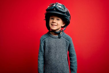 Young little caucasian kid wearing vintage biker motorcycle helmet and googles over red background with a happy and cool smile on face. Lucky person.