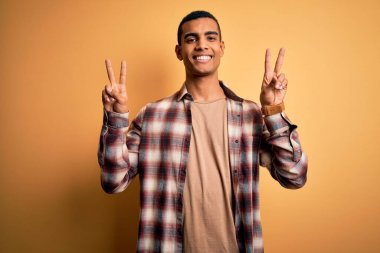 Young handsome african american man wearing casual shirt standing over yellow background smiling with tongue out showing fingers of both hands doing victory sign. Number two.