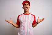 Young handsome african american sportsman wearing striped baseball t-shirt and cap crazy and mad shouting and yelling with aggressive expression and arms raised. Frustration concept.