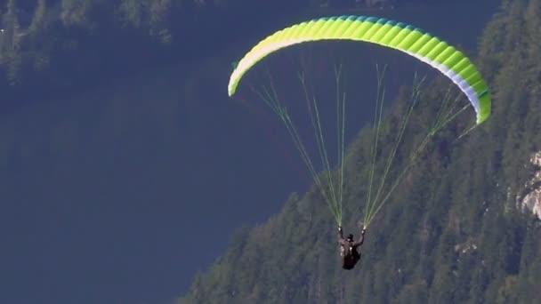 Fallschirmspringer oder Gleitschirm über den Bergen
