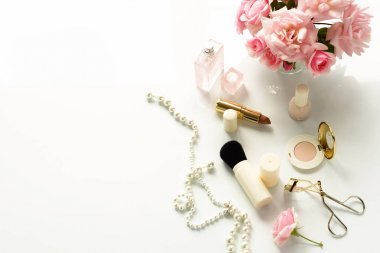 Beauty blog concept. Female make up accessories and bouquet of pink roses on white background. Flat lay, top view feminine desk, workspace . Copy space.