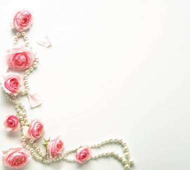 A frame of pink roses and beads on a white background.Top view. Copy space