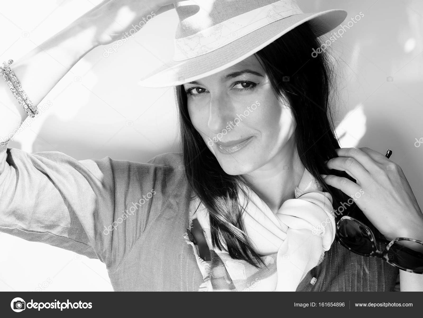 Black and white portrait of an adult beautiful elegant woman in a hat on a white background stock image