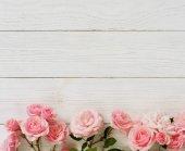 Fotografie Kytice z krásných růžových růží na bílém pozadí dřevěná. Pohled shora. Kopírovat prostor