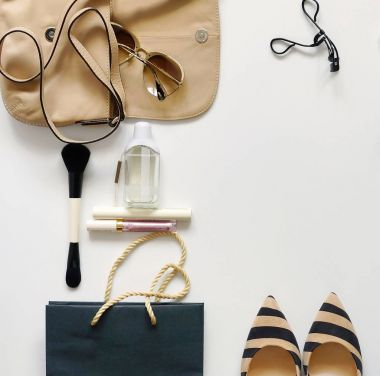 Top view of female fashion accessories.Beige handbag with sunglasses, high heel shoes,perfume and cosmetics on white background.