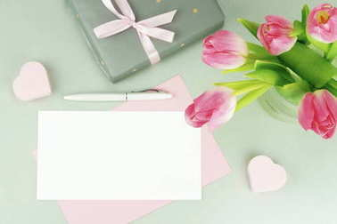 Feminine desk, workspace with a bouquet of beautiful pink tulips in a vase, a gift and a card for text on a gray background. flat lay. top view. copy space