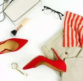 Fényképek lapos laikus női ruhákat és kiegészítőket kollázs blúz, nadrág, szemüveg, karóra, piros magas sarkú cipő fehér háttér. Másolja a hely. Szemközti nézet