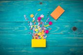 Exploding celebration yelow gift box on a wooden background. Holidays concept.