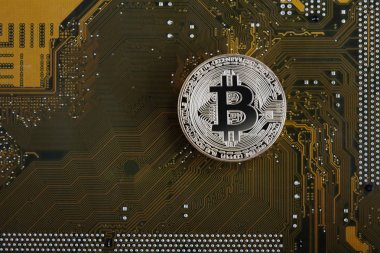 Gold bitcoin with microcircuits on a green background. The conce