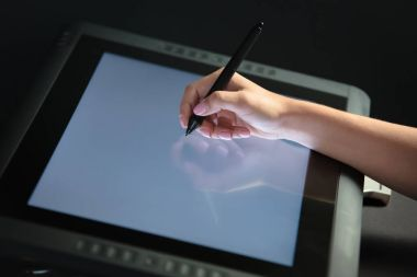 Woman hand drawing on professional graphic tablet. Black backgro