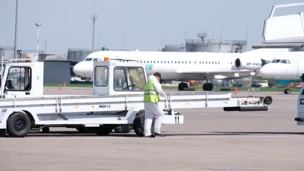 Almaty / Kazakhstan - 04.23.2020 : The driver of the mechanical ramp for the plane gets into the car
