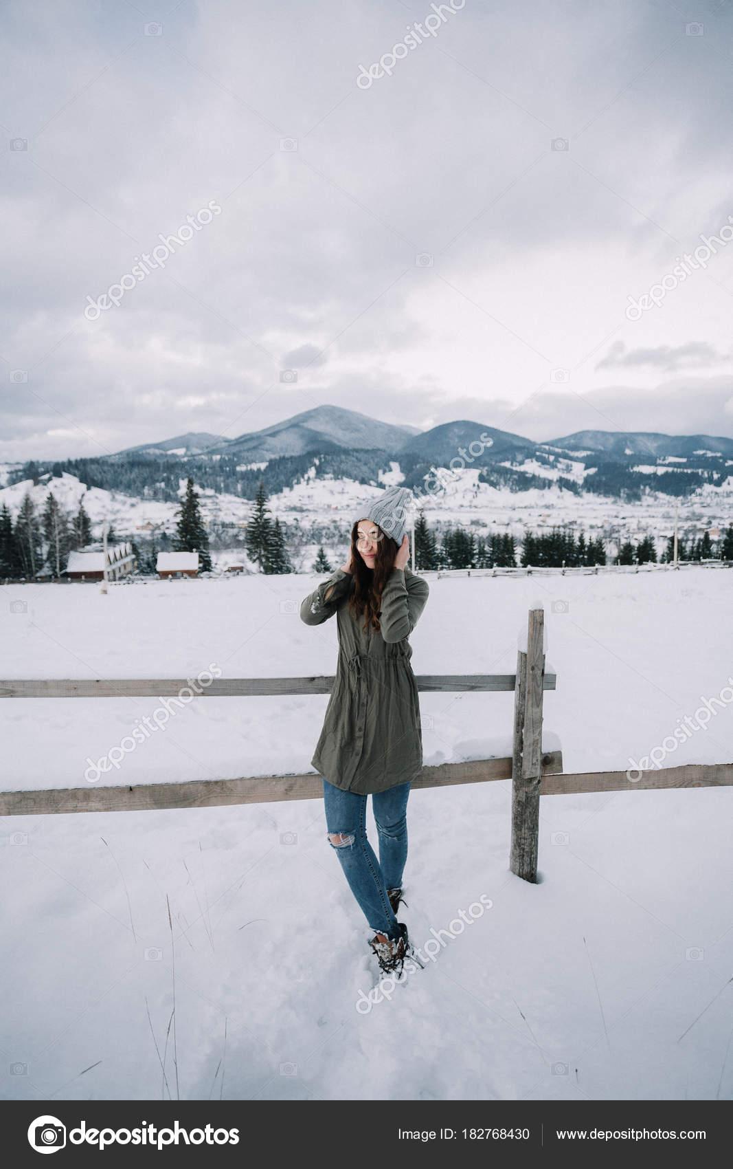 5d97b278a357 Happy νεαρό κορίτσι στο πράσινο πουλόβερ απολαμβάνει το χιόνι.  Διασκεδάζοντας στο χιόνι. Κοντά με όμορφες Χειμερινές εξοχικές κατοικίες σε  βουνά — Εικόνα ...