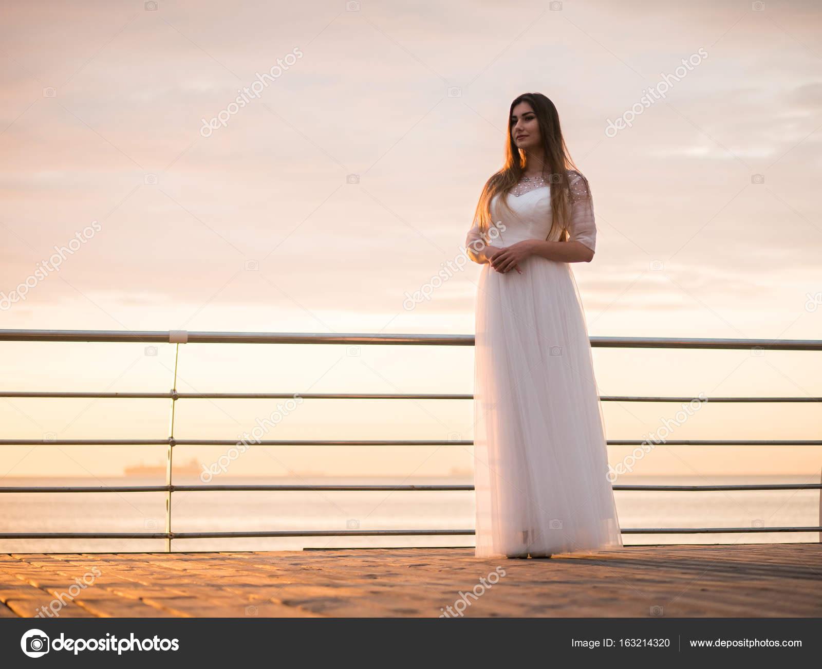 749dd4cded86c Chica de belleza sobre fondo de cielo en un vestido blanco cerca del mar.  hermosa novia