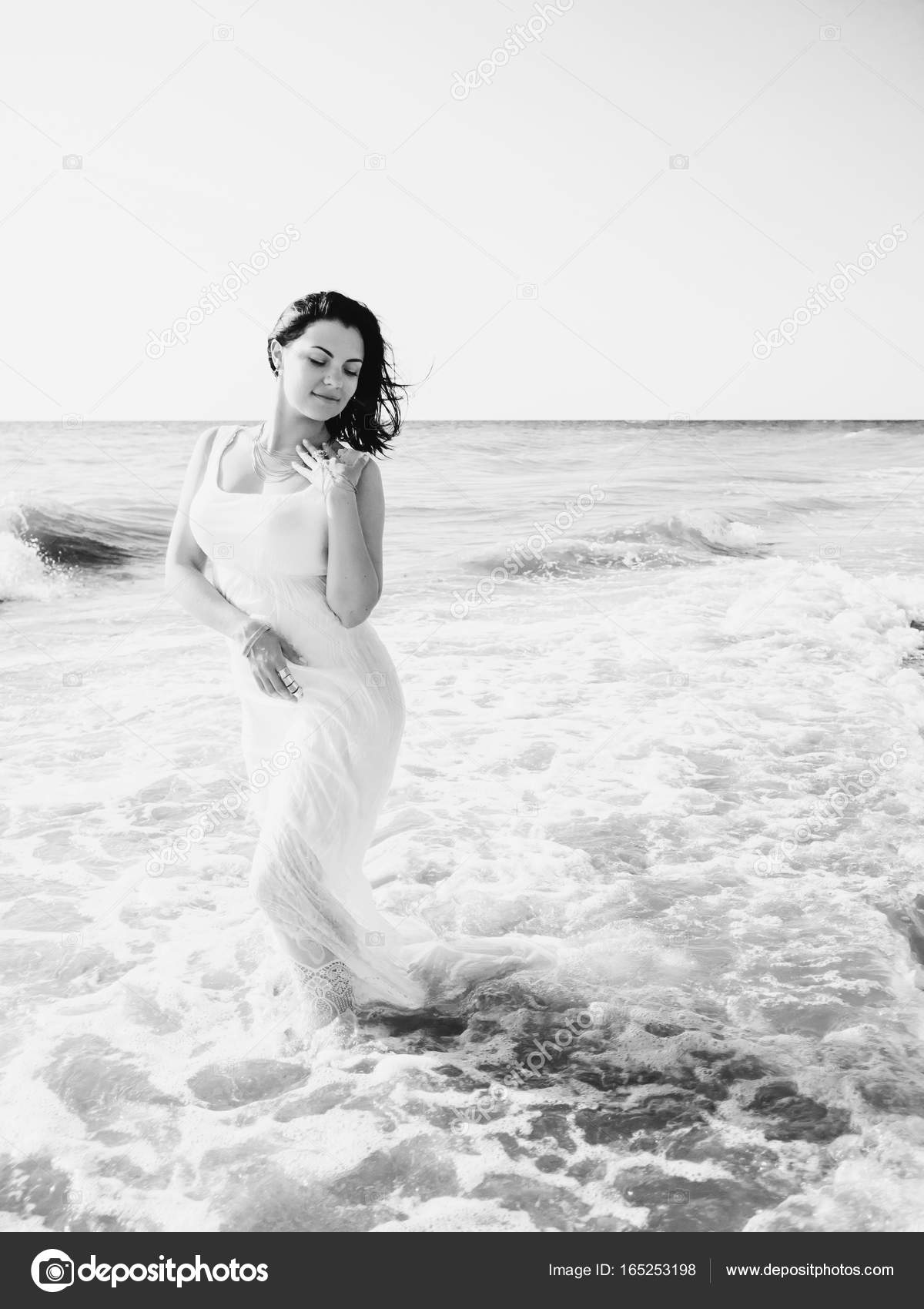 Gypsy young brunette girl in white maxi long dress standing on the waves in  sea or ... a77b35c99